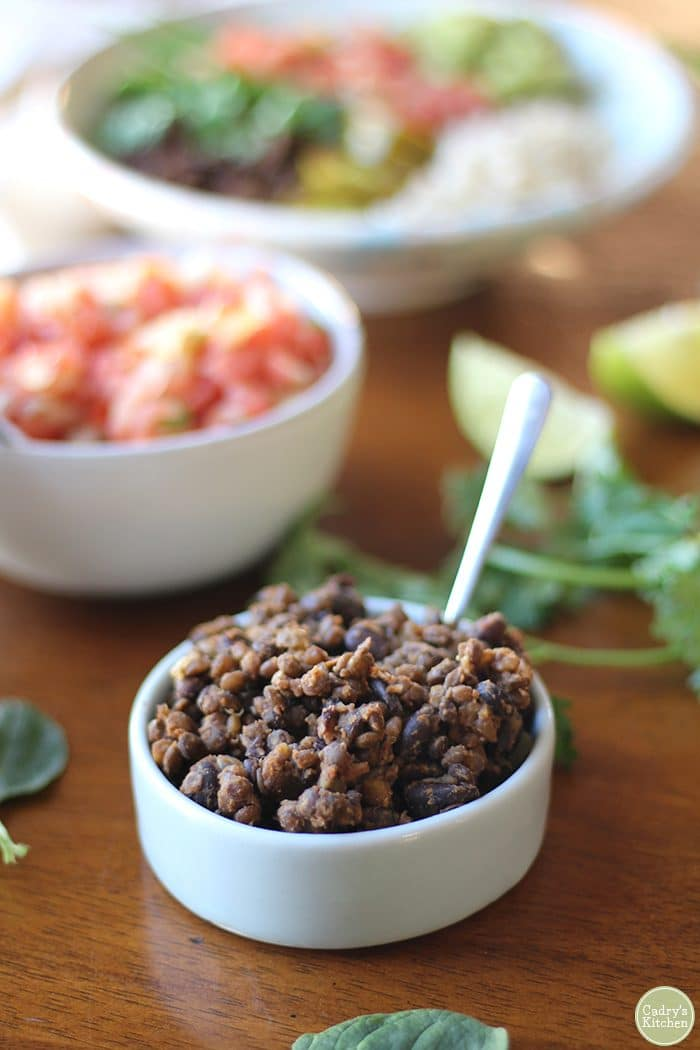 Black bean and lentil mixture in small bowl with spoon.