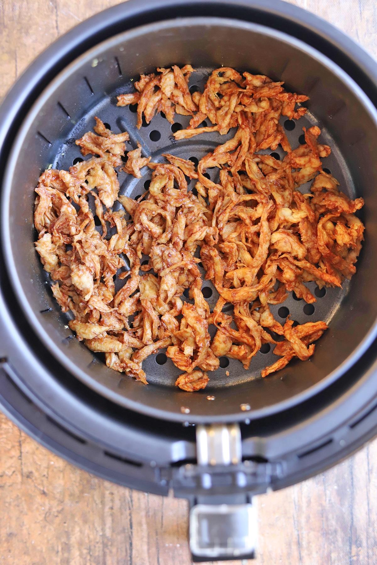 Barbecued Soy Curls in air fryer basket.