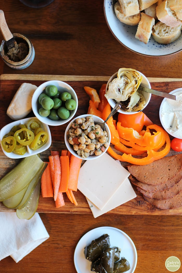 Vegan cheese board with pickles, carrots, and bell peppers.