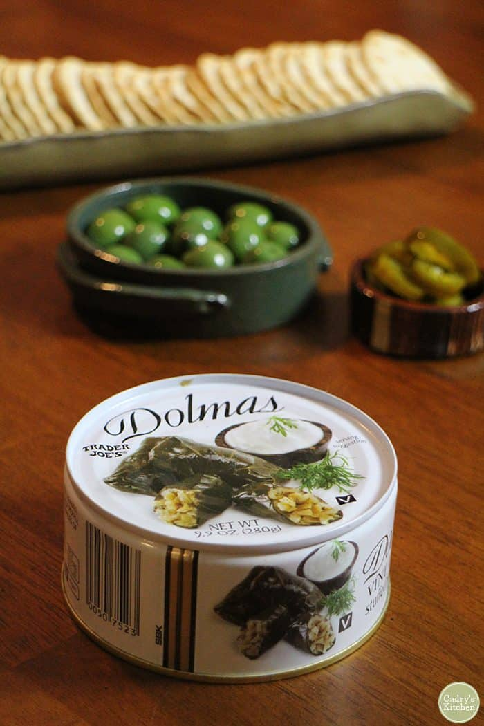 Can of dolmas from Trader Joe's with Castelvetrano olives and crackers.