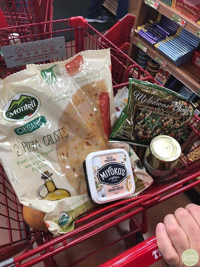 Trader Joe's shopping cart with pizza crust, Miyoko's cream cheese, and frozen vegetables.