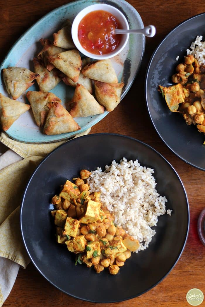 Samosas on plate next to curry and rice.