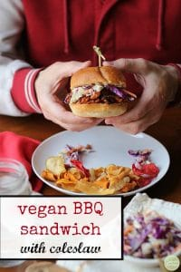 Text: Vegan BBQ sandwich with coleslaw. Hands holding sandwich over plate.