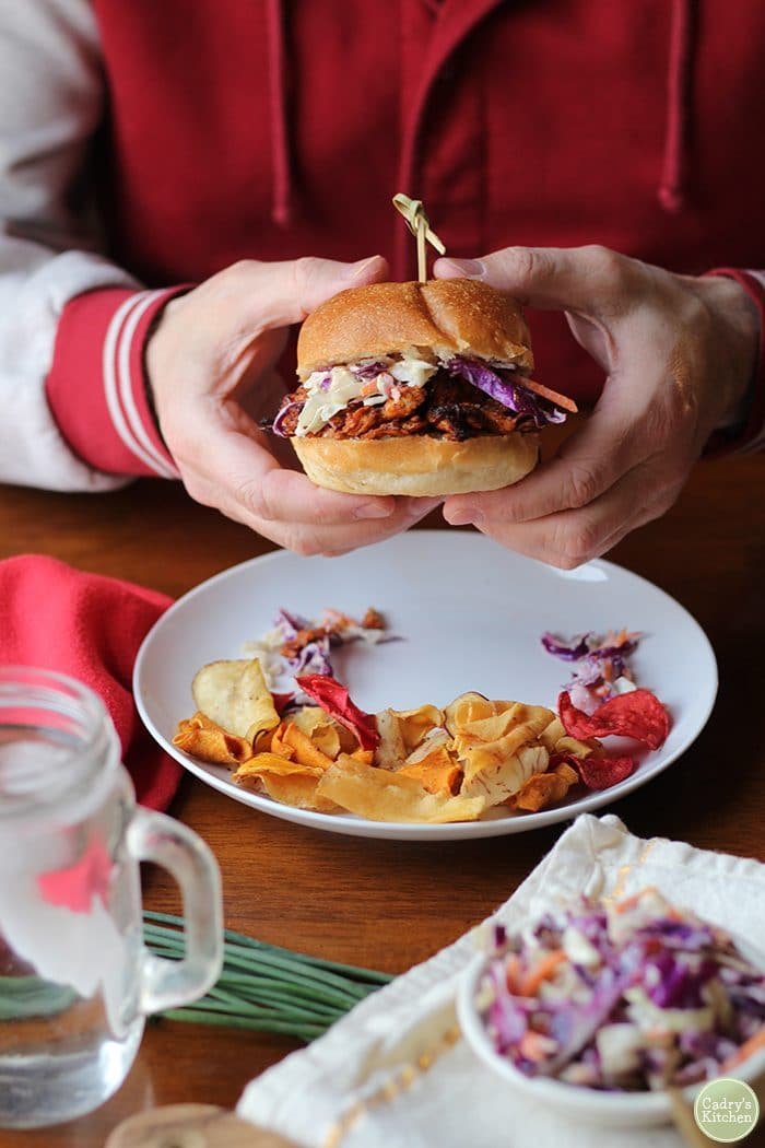 Hands holding vegan BBQ sandwich with cole slaw.