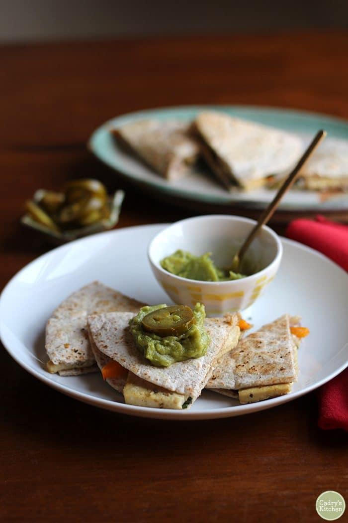 Vegan breakfast quesadilla with guacamole & jalapeno pepper slices.