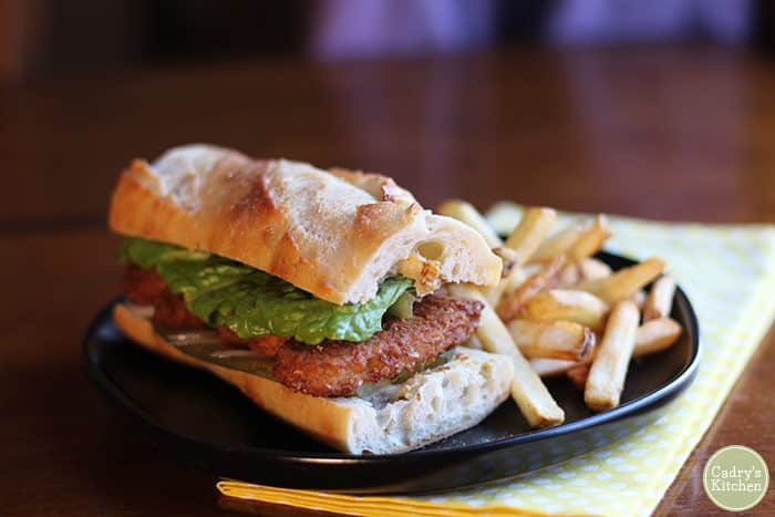 Vegan chicken sandwich on baguette with french fries.