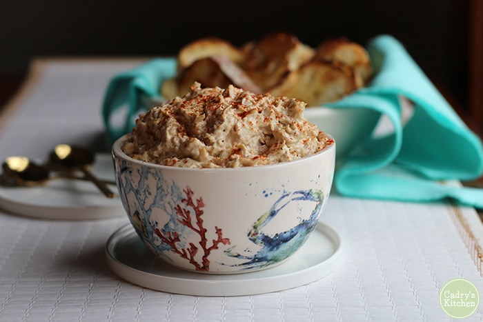 Small bowl with vegan crab dip, bread, and spoons.