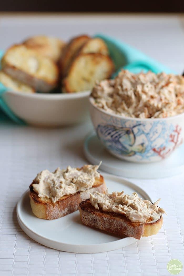 Crostini with vegan crab dip on small plate. Bowl of vegan crab dip & bread in background.