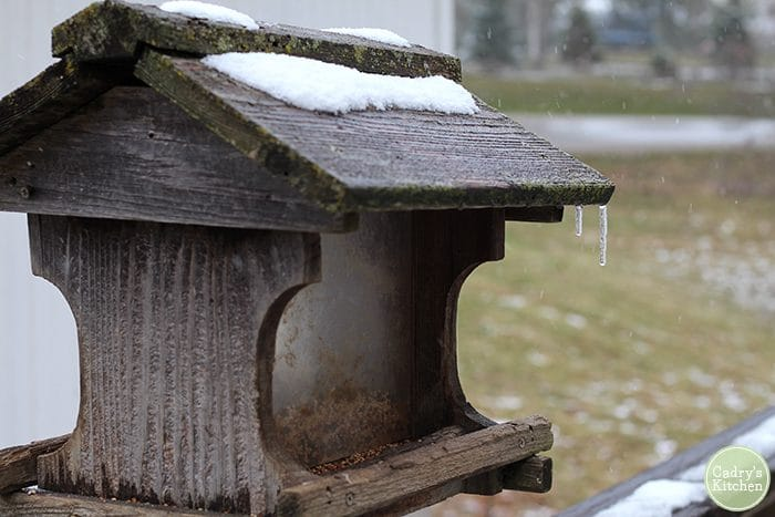 Bird house covered in snow with an icicle hanging off it.