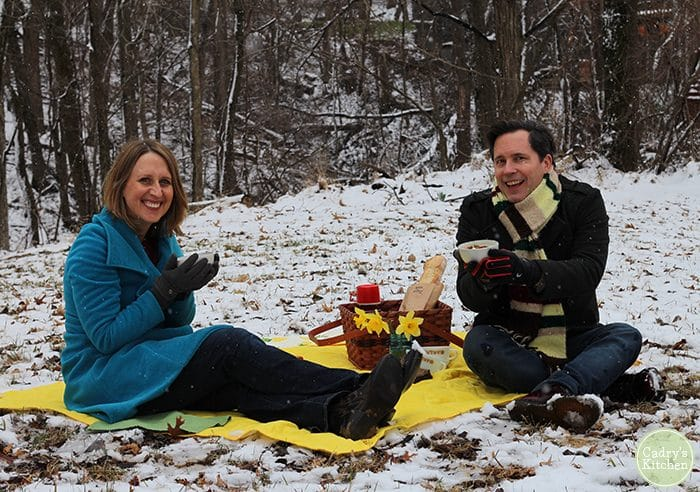 Cadry and David at snow picnic with blanket and bowls of vegan baked potato soup.