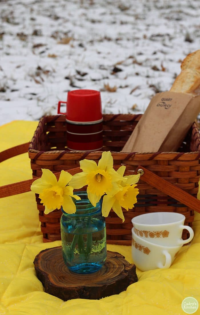 Daffodils in mason jar, picnic basket, thermos, and bread on picnic blanket for a winter picnic.