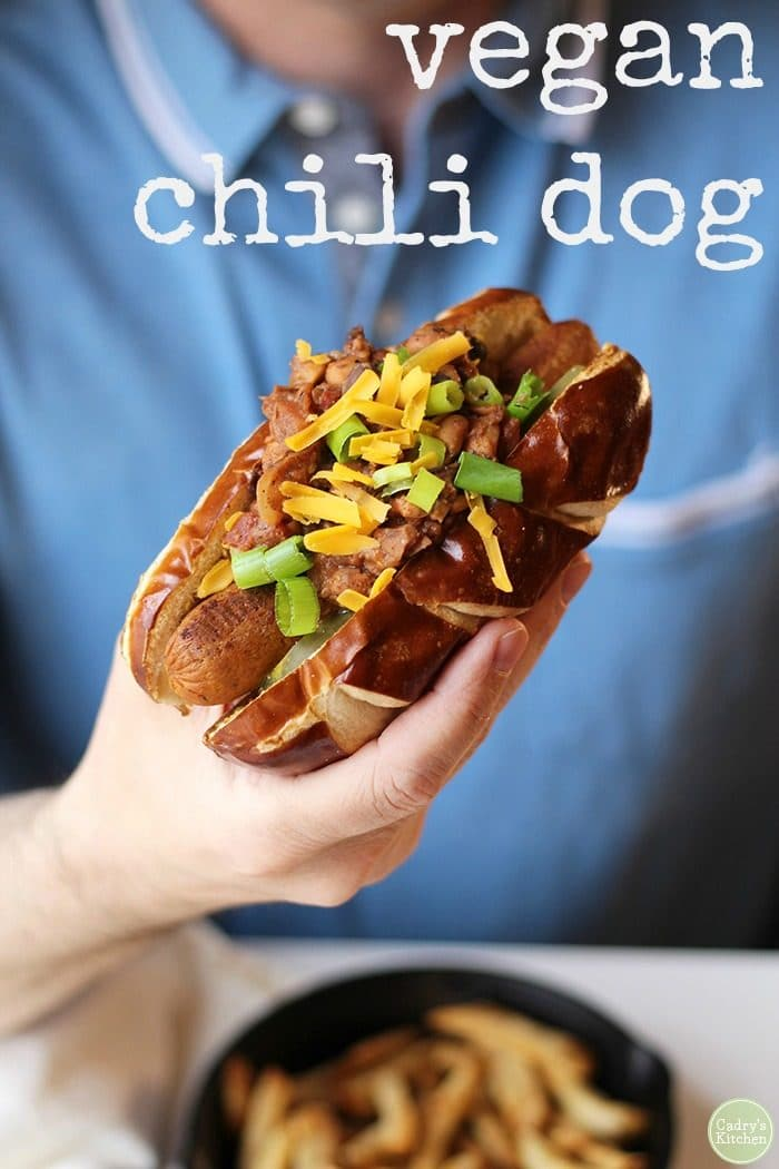 Hand holding vegan chili dog with non-dairy cheese and onions.