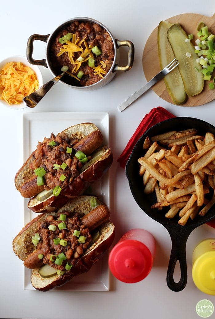Overhead vegan chili dogs on table with fries, pickles, onions, three bean chili, ketchup, and mustard.