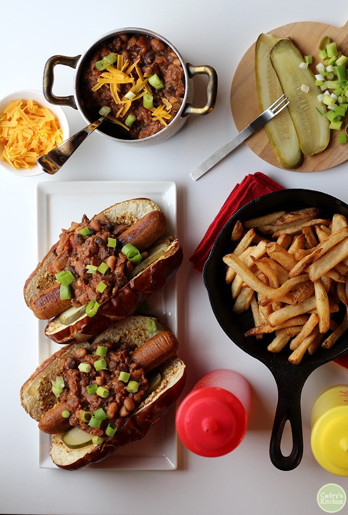 Overhead chili dogs on table with fries, pickles, onions, three bean chili, ketchup, and mustard.