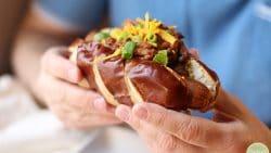 Hands holding vegan chili dog with three bean chili, vegan cheese, and onions.