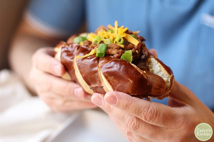 Hands holding vegan chili dog with three bean chili, vegan cheese, and onions.