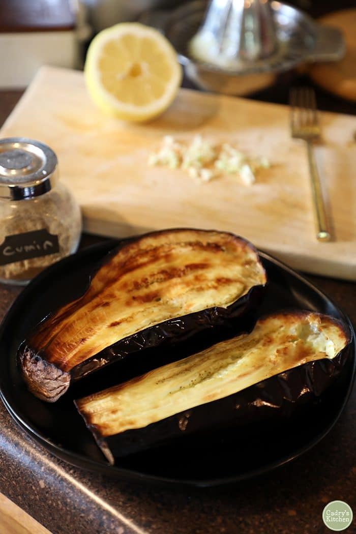 Eggplant sliced in half, roasted on plate. Cumin, garlic, and lemon in background.