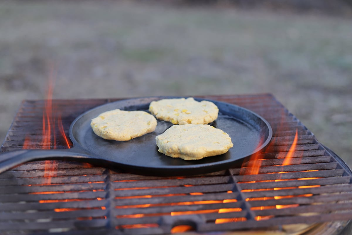 Corn cakes on a cast iron skillet on a fire.