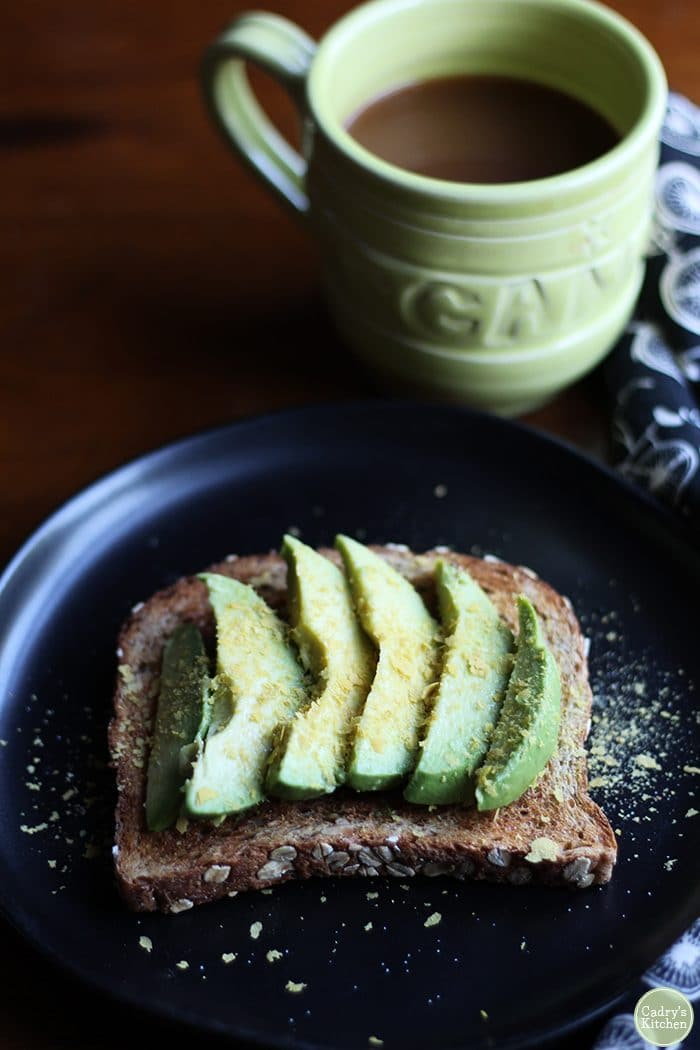 Avocado toast with nutritional yeast flakes & coffee in mug.