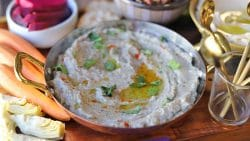 Eggplant dip in serving bowl by turnip pickles and carrots.