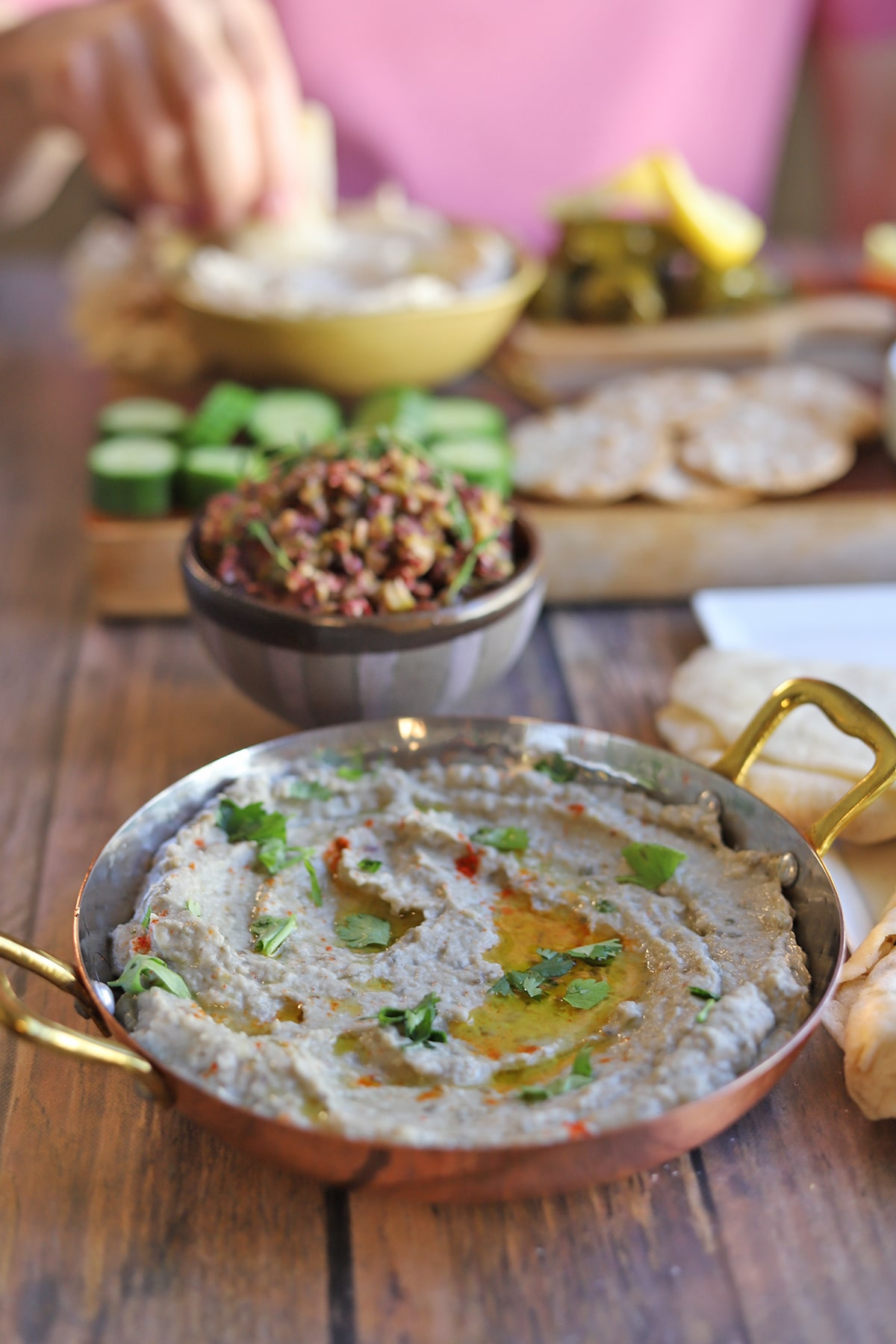 Vegan baba ganoush in gold serving bowl by olive tapenade.