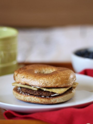 Breakfast sandwich on plate made with rosemary olive oil bagel, non-dairy cream cheese, eggy tofu, and Gardein breakfast patty.