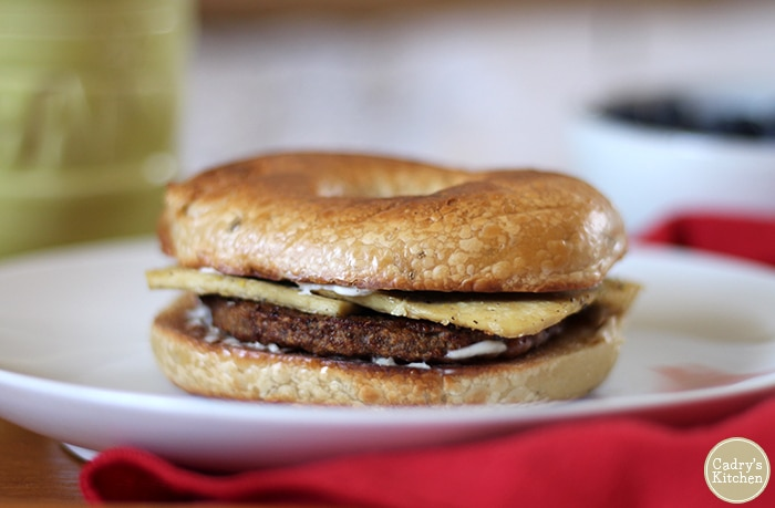 Close-up vegan breakfast sandwich with eggy tofu, vegan sausage, and non-dairy cream cheese.
