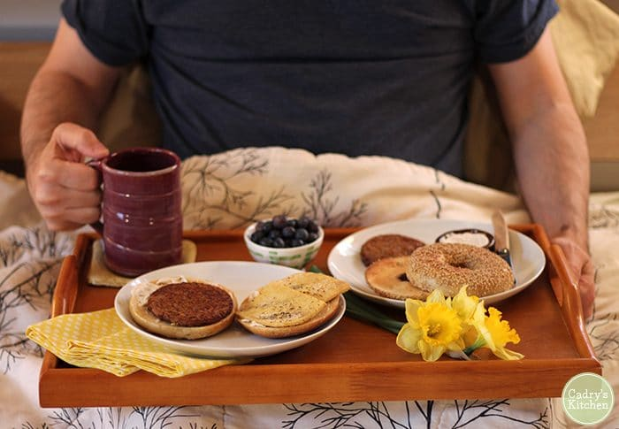 Breakfast tray with vegan breakfast sandwich, bagels, coffee, and blueberries.