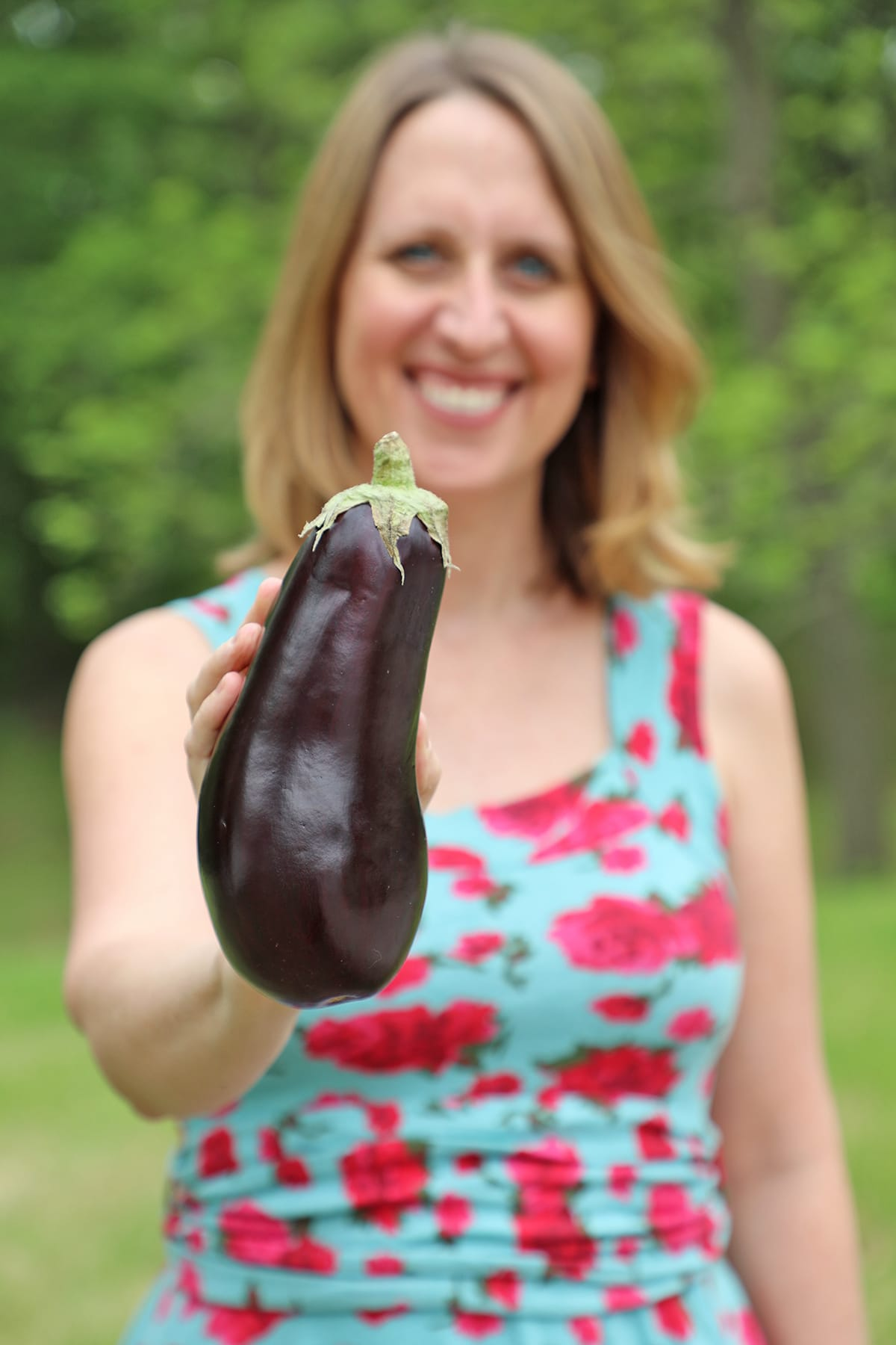 Cadry holding globe eggplant.