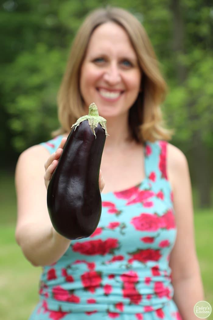 Cadry holding eggplant.