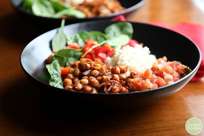 Vegan burrito bowl with spicy chickpeas, spinach salad, and rice in black bowl.
