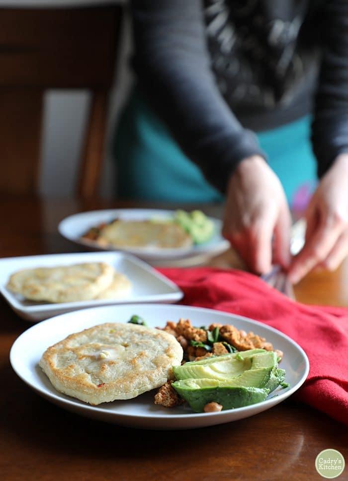 Vegan corn cakes on plate with avocado and tofu scramble.