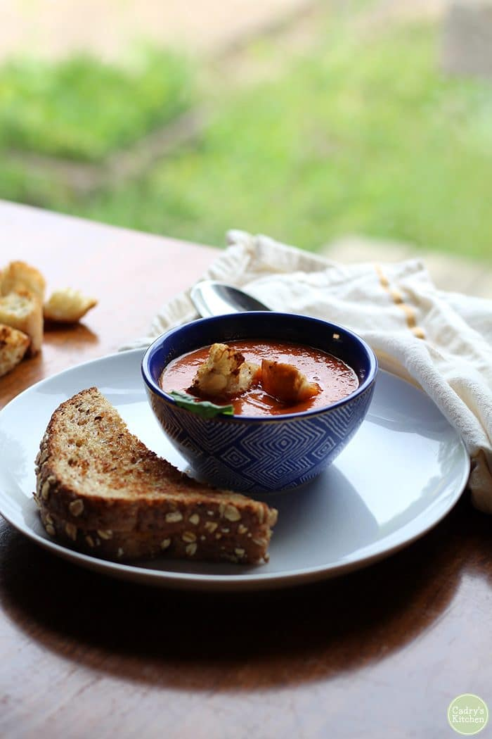 Vegan grilled cheese sandwich and creamy tomato soup by window.