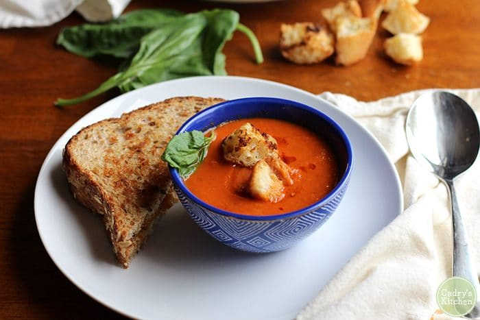 Croutons and basil on creamy vegan tomato soup with non-dairy grilled cheese sandwich.