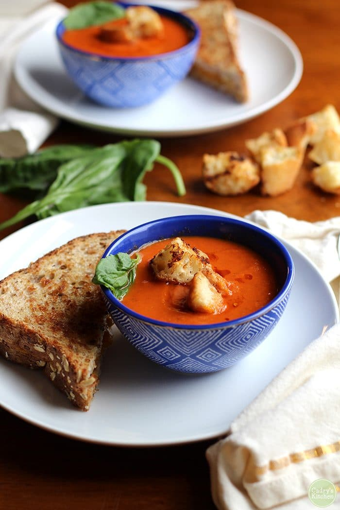 Creamy vegan tomato soup in blue bowl with half of a grilled cheese sandwich.
