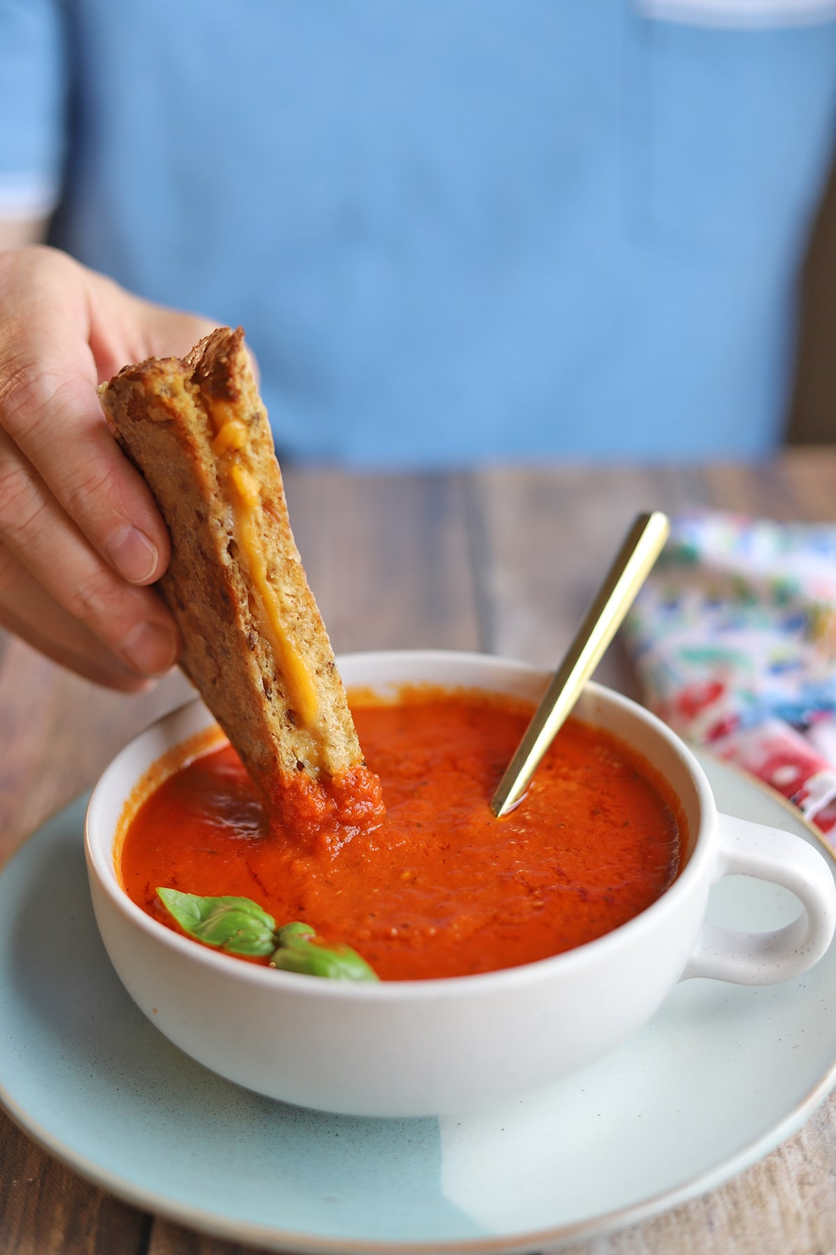 Hand dunking grilled cheese sandwich into soup.