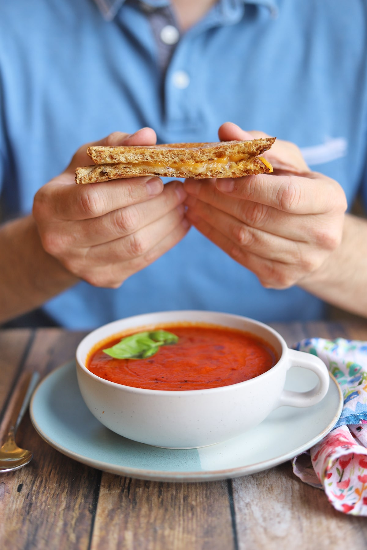 Hands holding grilled cheese sandwich over bowl of soup.