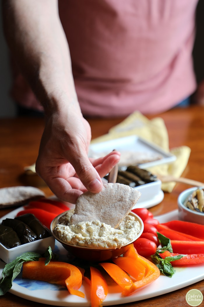 Hand dipping pita bread into baba ganoush.
