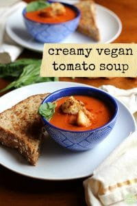 Vegan creamy tomato soup in bowl with croutons. Grilled cheese sandwich on plate + text.