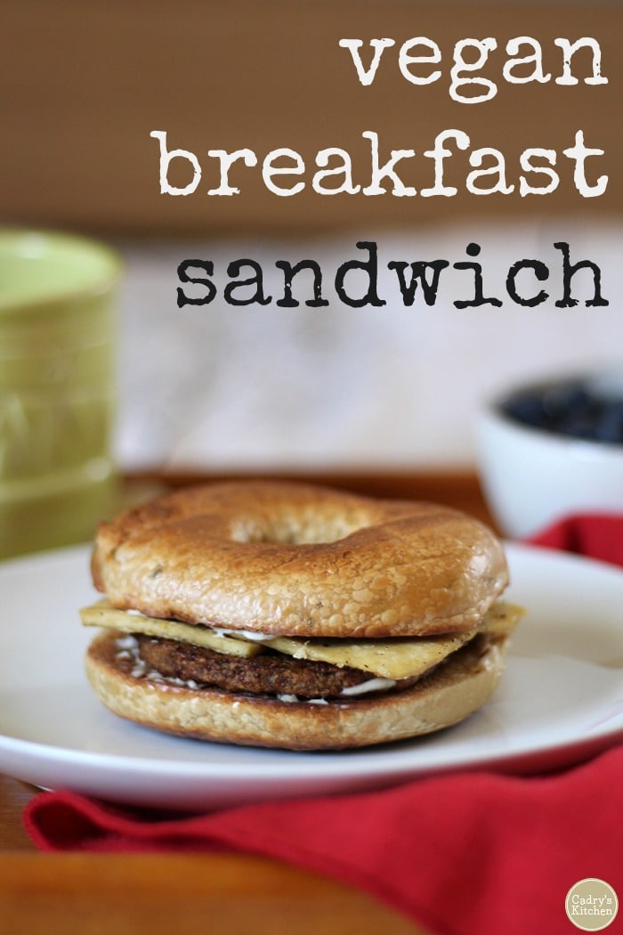 This vegan breakfast sandwich with thinly sliced eggy tofu, non-dairy cheese, and veggie sausage is wonderfully filling & perfectly portable. #vegan #breakfast #bagel