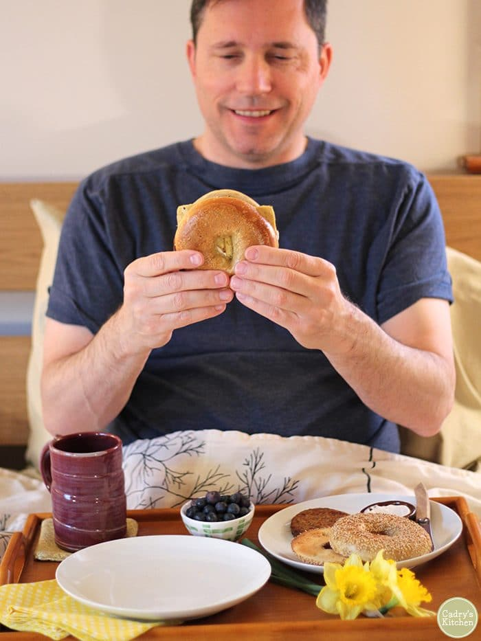 David in bed with breakfast tray holding vegan breakfast sandwich.