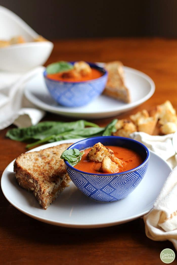 Croutons on top of creamy vegan tomato soup in blue bowl. Non-dairy grilled cheese on plate.