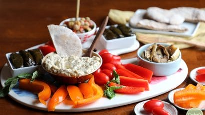 Air fryer eggplant dip (baba ganoush) on a platter with bell peppers, chickpeas, dolmas, and grape tomatoes.