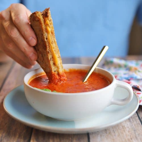Grilled cheese being dipped into bowl of vegan tomato soup.