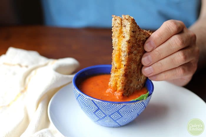 Hand dipping vegan grilled cheese sandwich into vegan creamy tomato soup.