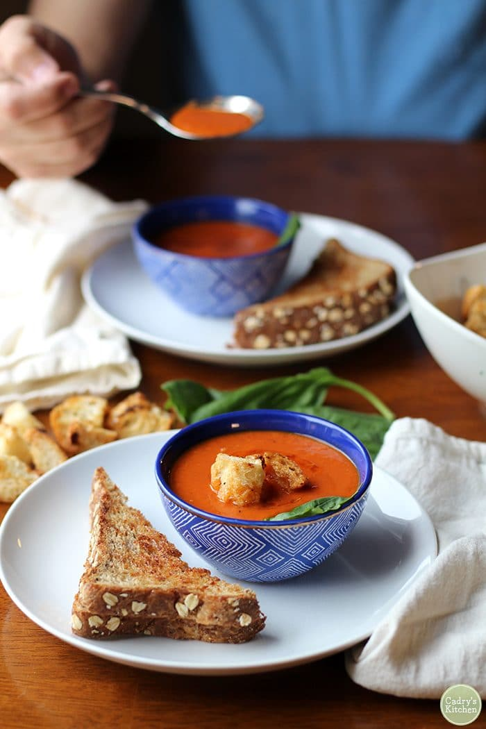 Vegan creamy tomato soup in bowl alongside non-dairy grilled cheese.