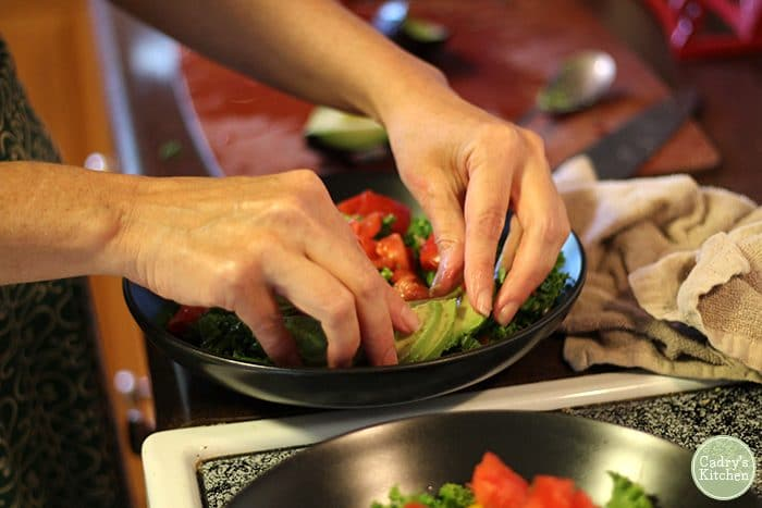 Hands laying avocado on a salad.