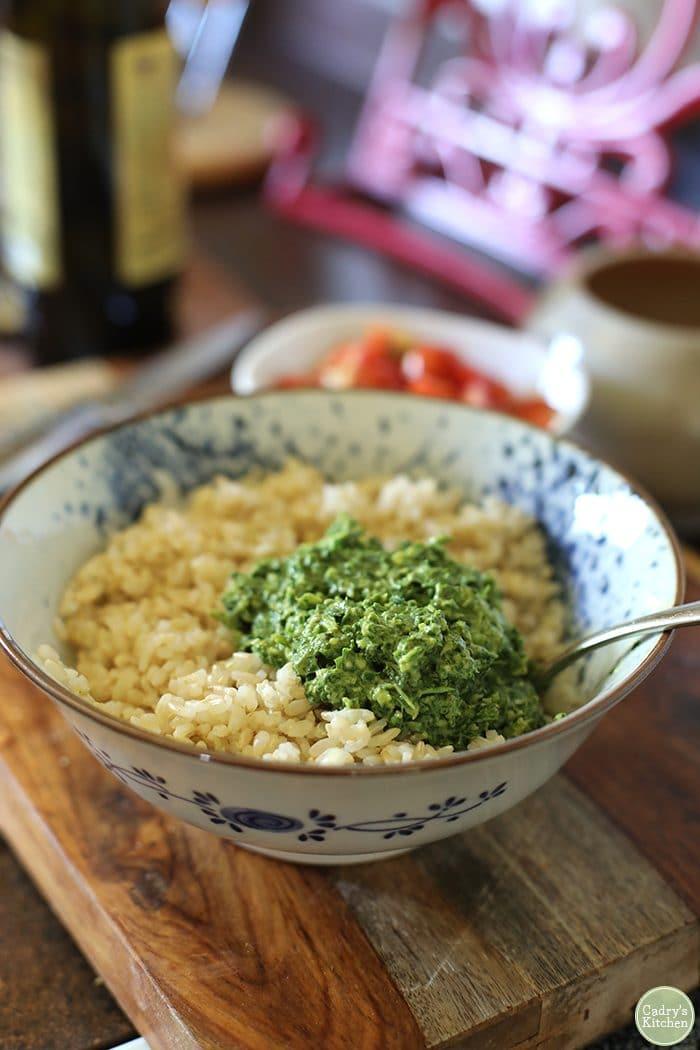 Vegan basil pesto on brown rice in bowl.