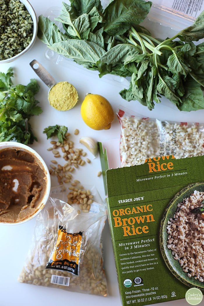 Ingredients for vegan pesto rice - including Trader Joe's frozen brown rice, pine nuts, miso paste, lemons, nutritional yeast flakes, basil, and cilantro.