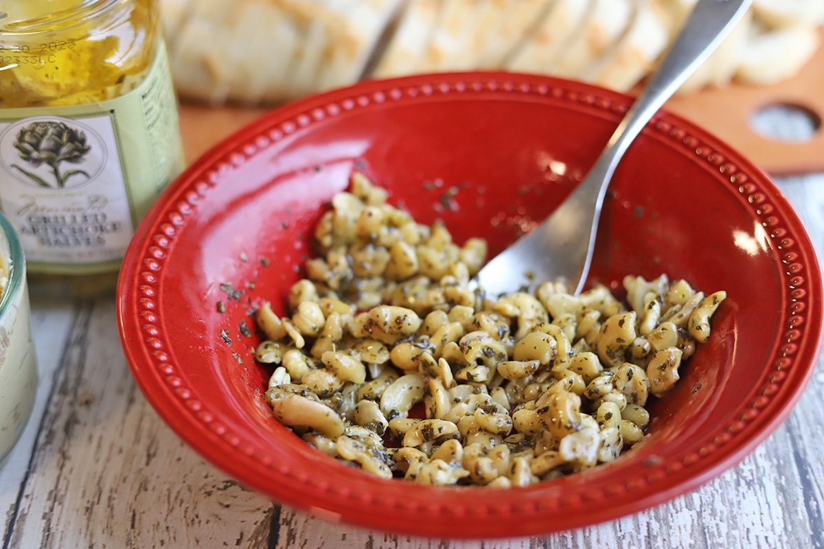 Cashew pieces marinating in seasonings in bowl.